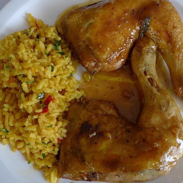 Pollo guisado con salsa suave de cebolla acompañado de arroz con verduras y cilantro.