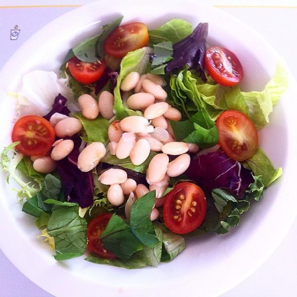 Ensalada de judías verdes, judías blancas, brotes verdes y tomate cherry.