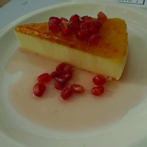Tarta de queso con granos de granada y almíbar suave de fresa.