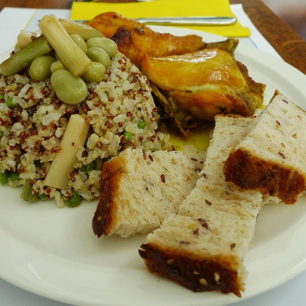 Pollo asado con Ras-el-hanout,arroz integral con quinoa dorada,salteado con habas, espárragos y ajos tiernos, acompañado de pan con sésamo.