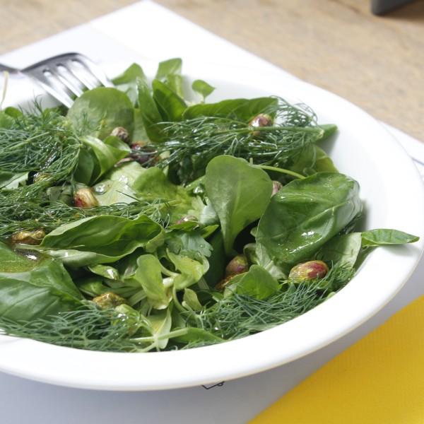 Ensalada de hoja verde, albahaca, cilantro, eneldo,  con pistachos pelados, con aliño de aceite virgen , zumo de limón y agua de azahar.
